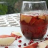 Glass of White Sangria with nectarines and pomegranate seeds