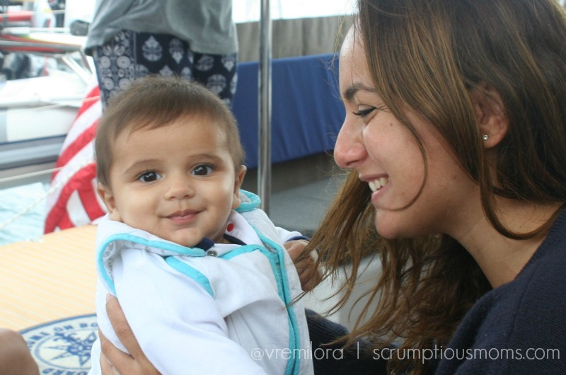 Alexandra smiling as she holds a little one