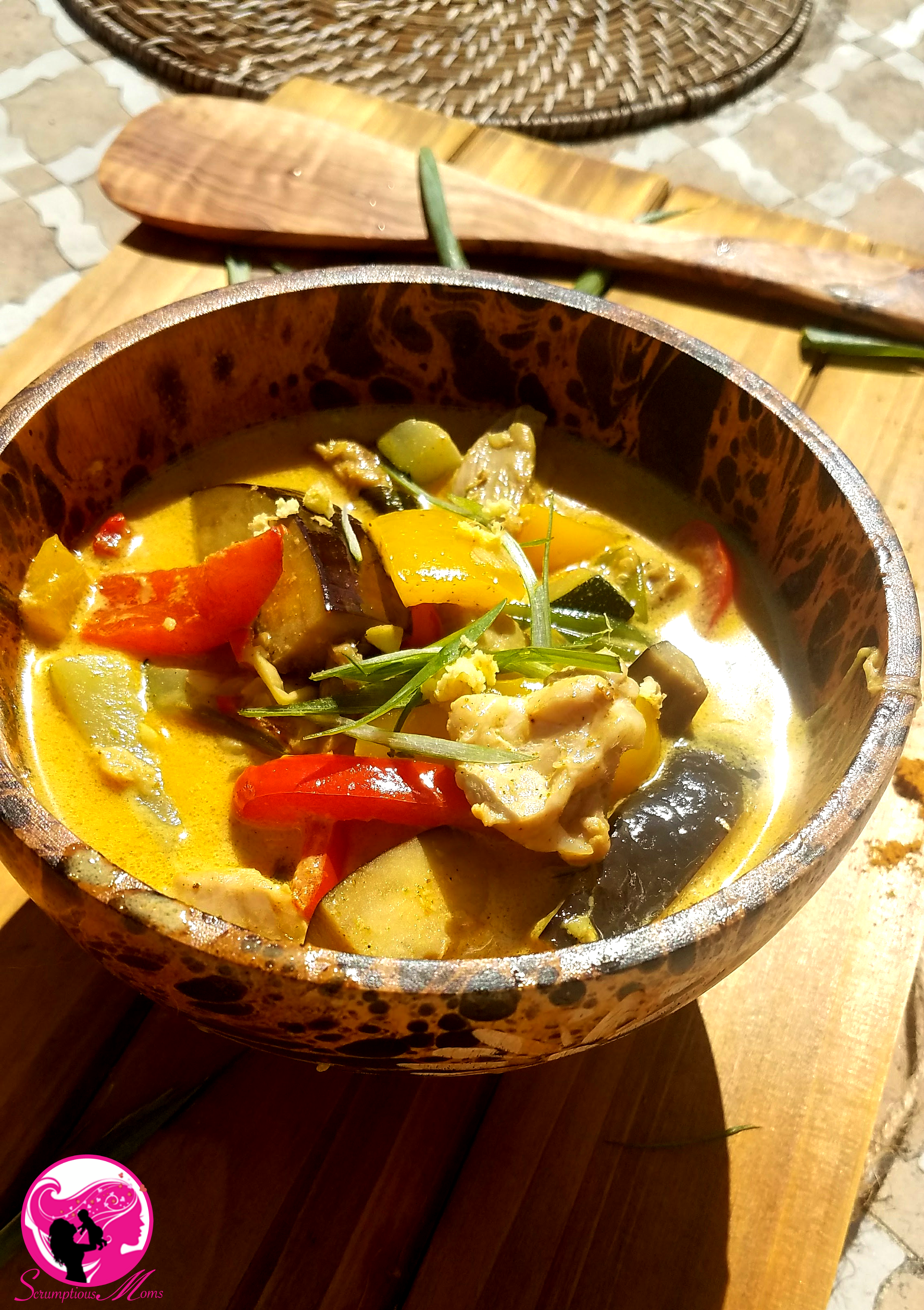 Bowl of yellow coconut curry with chicken and vegetables